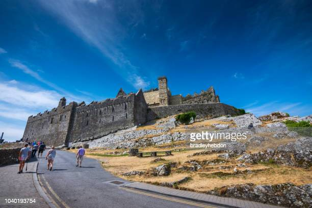 Tourists walk up the hill towards the entrance of the medieval ruins at Rock of Cashel