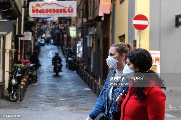 Tourists walk wearing antivirus masks to protect themselves from the Coronavirus in the city of Naples.
