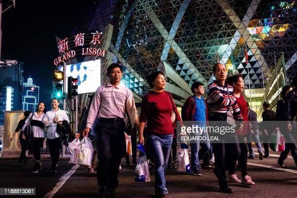 Tourists walk with shopping bags in front of Grand Lisboa Casino in Macau on December 15 2019