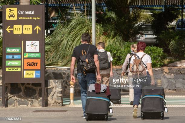 Tourists walk with their luggage upon their arrival from different European cities, especially from the United Kingdom and Germany, to the Reina...
