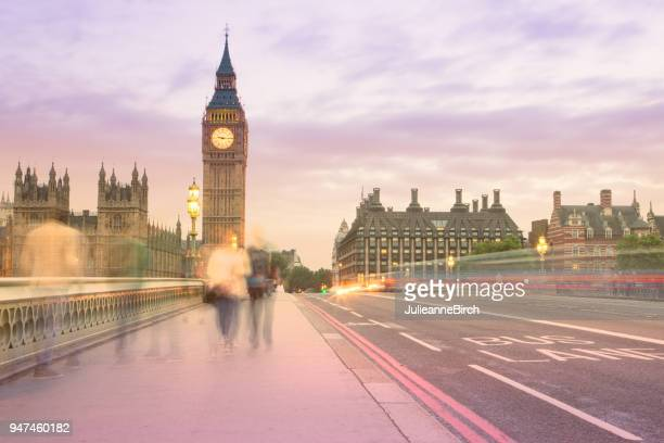 Tourists walking across Westminster Bridge at dusk with Big Ben in background, London