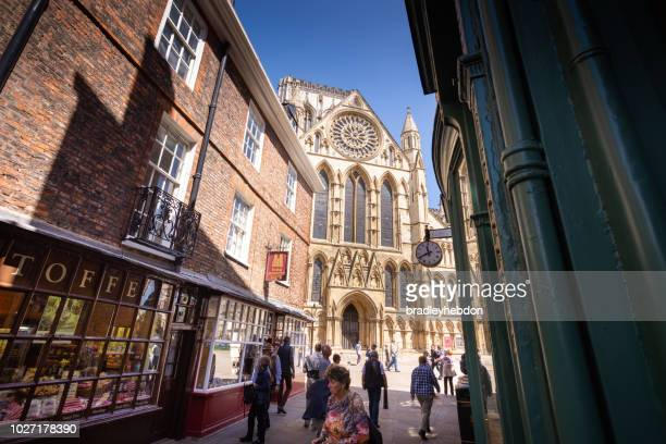 tourists walking along the narrow streets of york in england - york minster stock photos and pictures