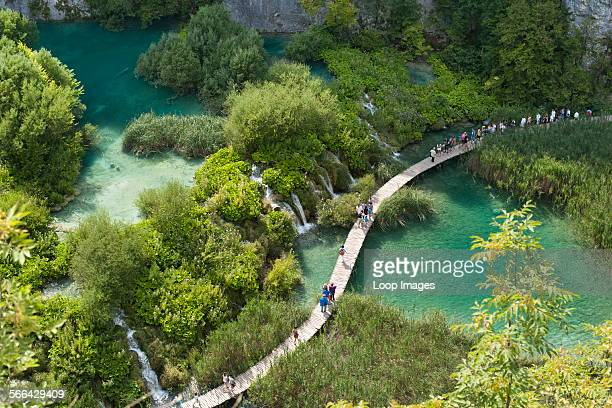 Tourists walking along wooden walkways in Plitvice Lakes National Park in Croatia