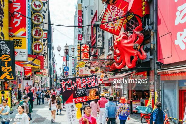 Tourists walking around crowded Osaka Dotonbori entertainment district
