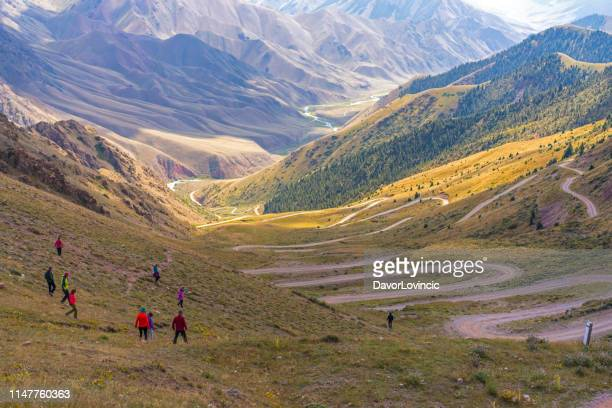 tourists walking down the  33 parrots pass in kyrgyzstan - kyrgyzstan stock pictures, royalty-free photos & images