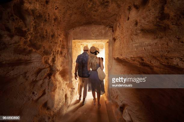 Tourists walking in dark passage at archaeological site in Greece