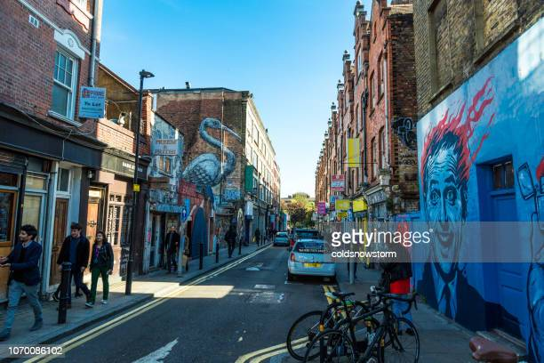 tourists walking in the crowded street of brick lane, london, uk - east london stock pictures, royalty-free photos & images