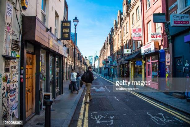 Turistas caminando por la concurrida calle de Brick Lane, Londres, Reino Unido
