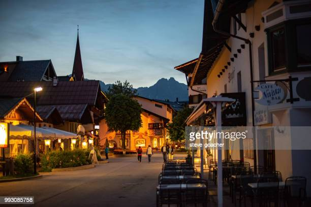 tourists walking in the illuminated streets of seefeld, austria, in the evening. - seefeld stock photos and pictures