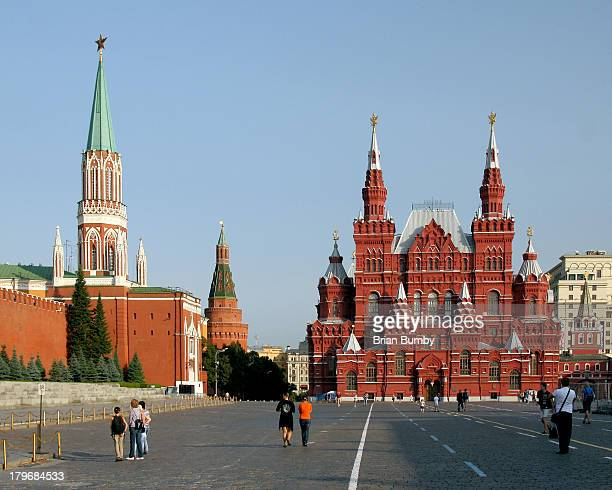 Tourists walking in the morning in Red Square in Moscow, Russia, with gates of Kremlin and the Historical Museum in background.