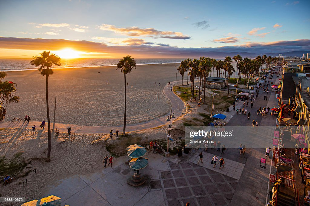 Tourists walking on footpath by beach during sunset : Stock Photo