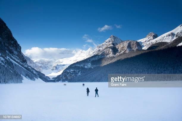 tourists walking on frozen lake. - lake louise lake stock pictures, royalty-free photos & images