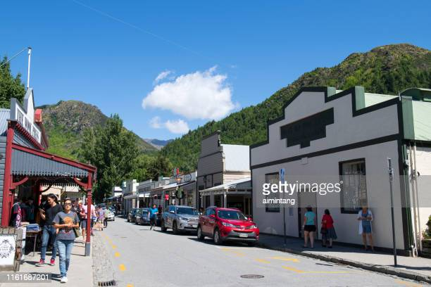 tourists walking on street in arrowtown - arrowtown stock pictures, royalty-free photos & images