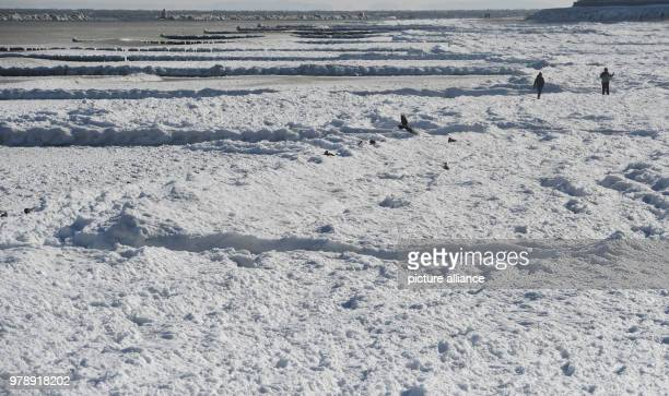 Tourists walking on the frozen waves of the Baltic Sea off the Seebruecke bridge in Koserow, Germany, 01 March 2018. Local temperatures may rest at...