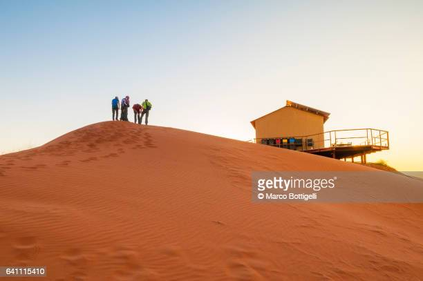 Tourists walking on top of a dune at sunset. Namibia