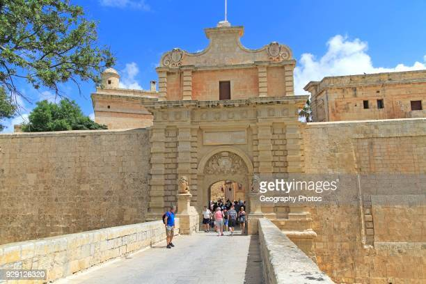 Tourists walking over moat bridge through entrance gateway of medieval city of Mdina Malta