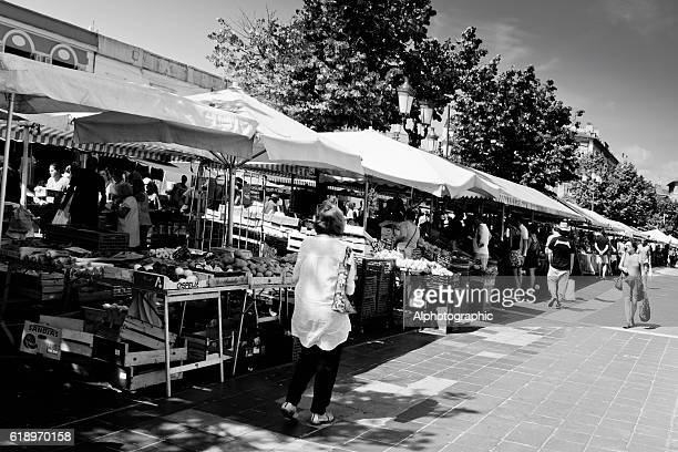 tourists walking past market stalls. - black and white vegetables stock photos and pictures