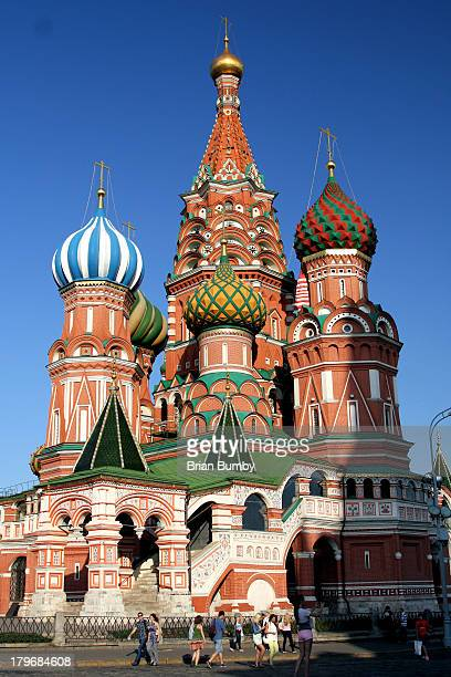 CONTENT] Tourists walking past St Basil's Cathedral in Red Square Russia in bright afternoon light