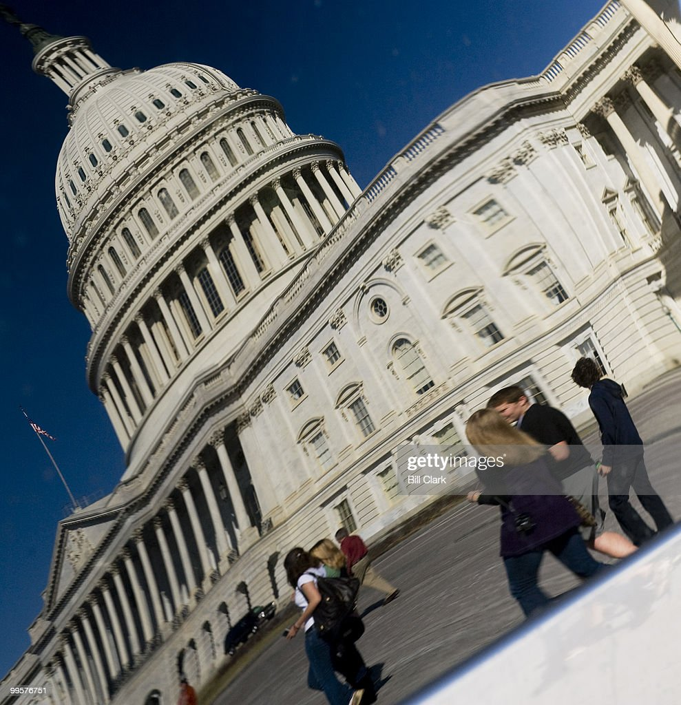 Tourists walking past the East Front of the Capitol are shown in a car's window reflection on Monday, March 9, 2009.