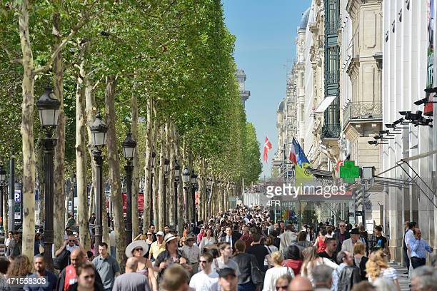 tourists walking the famous shopping street champs-elysees in paris, france - avenue des champs elysees stock photos and pictures