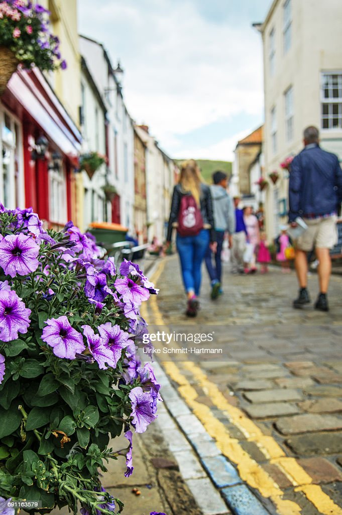 Tourists walking through the town of Staithes : Stock Photo