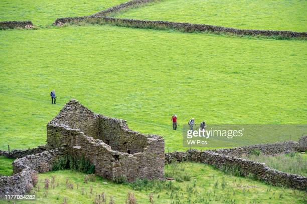 Tourists walking through the Yorkshire Dales in Yorkshire, England, UK.