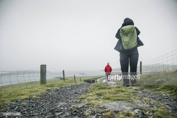 tourists walking to banna minn beach - north stock pictures, royalty-free photos & images