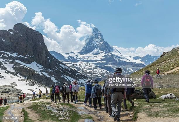 tourists walking toward matterhorn - tourismus stock-fotos und bilder