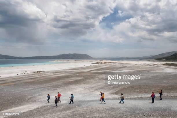 tourists walking towards the beach at lake salda,burdur. - emreturanphoto stock pictures, royalty-free photos & images