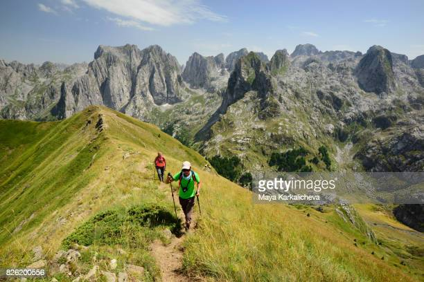 Tourists walking up a ridge in Prokletije mountain, Montenegro