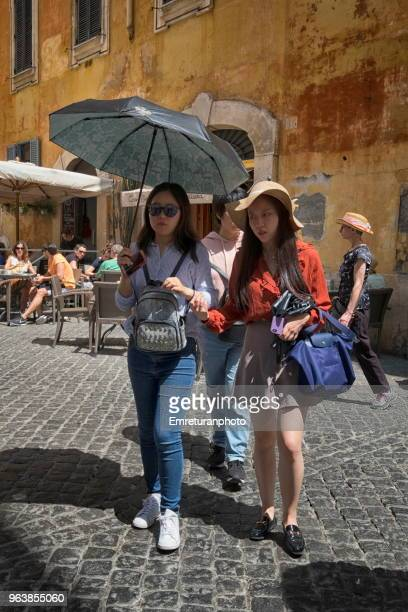 tourists walking with umbrella under strong rome sun. - emreturanphoto stock pictures, royalty-free photos & images