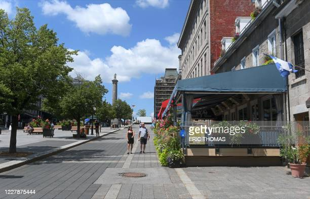 Tourists walks down Place Jacques-Cartier in Old-Montreal, Canada on July 28, 2020. - Stripped of the crowds of visitors that usually flock to its...