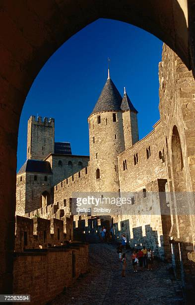 tourists wander around ramparts of medieval walled city, carcassonne, france - guy carcassonne photos et images de collection