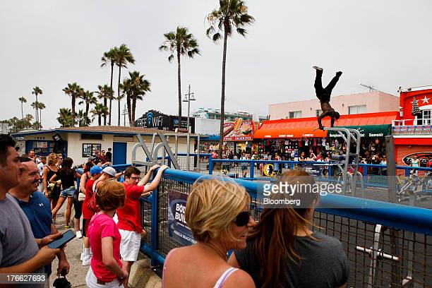 Tourists watch a bodybuilder perform an aerial workout at the Muscle Beach gym on Venice Beach in Los Angeles California US on Wednesday Aug 14 2013...