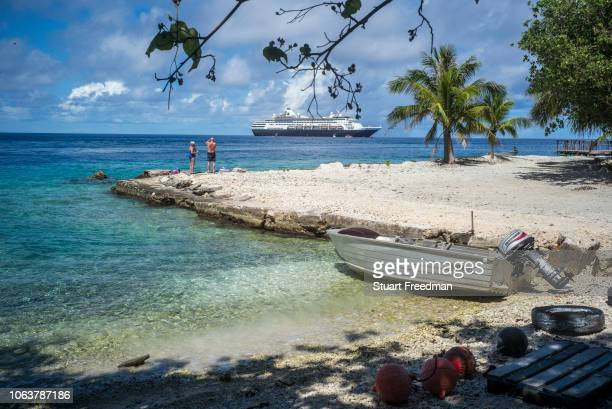 Tourists watch a cruise ship docked off Avatoru Rangiroa French Polynesia Rangiroa is one of the largest atolls in the world whose survival depends...