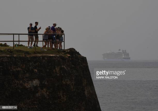 Tourists watch a cruise ship leaving beside the El Morro Fortress on May 16 2017 in San Juan Puerto Rico as the former Spanish colony of 35 million...