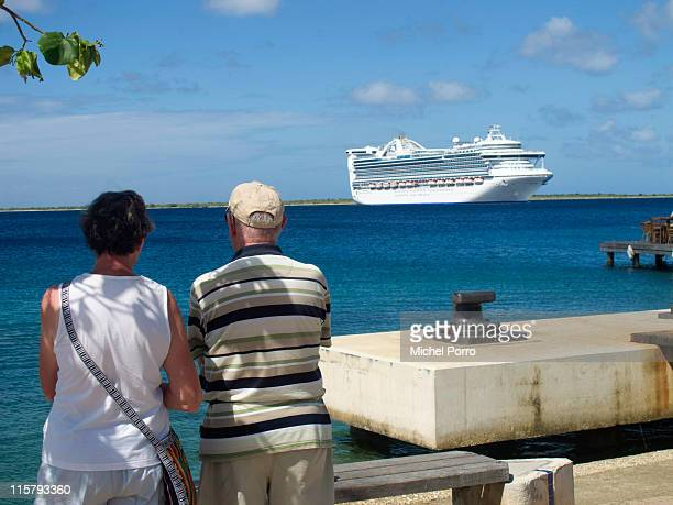 Tourists watch a cruise ship sail into Kralendijk harbour on February 3, 2011 on the island of Bonaire. Bonaire has earned a reputation for being one...