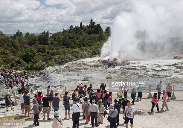 Tourists watch a geyser in the Whakarewarewa Geothermal Valley, Rotorua, New Zealand