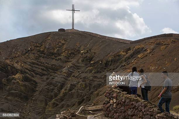 Tourists watch a lava lake inside the crater of the Masaya Volcano in Masaya some 30km from Managua on May 19 2016 Hundreds of tourists arrive daily...