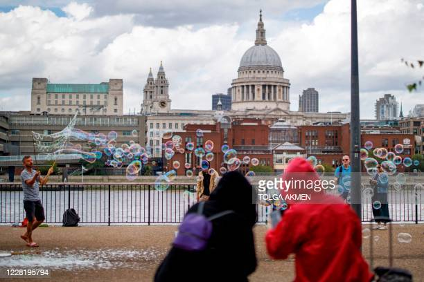 Tourists watch a street entertainer performing on Southbank in central London on August 24 2020 For those tourists who do run the gauntlet of...