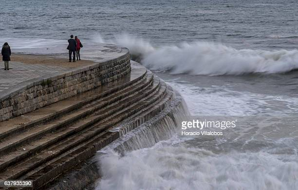 Tourists watch and take pictures as waves break at Praia da Duquesa in stormy weather on January 03 2017 in Cascais Portugal