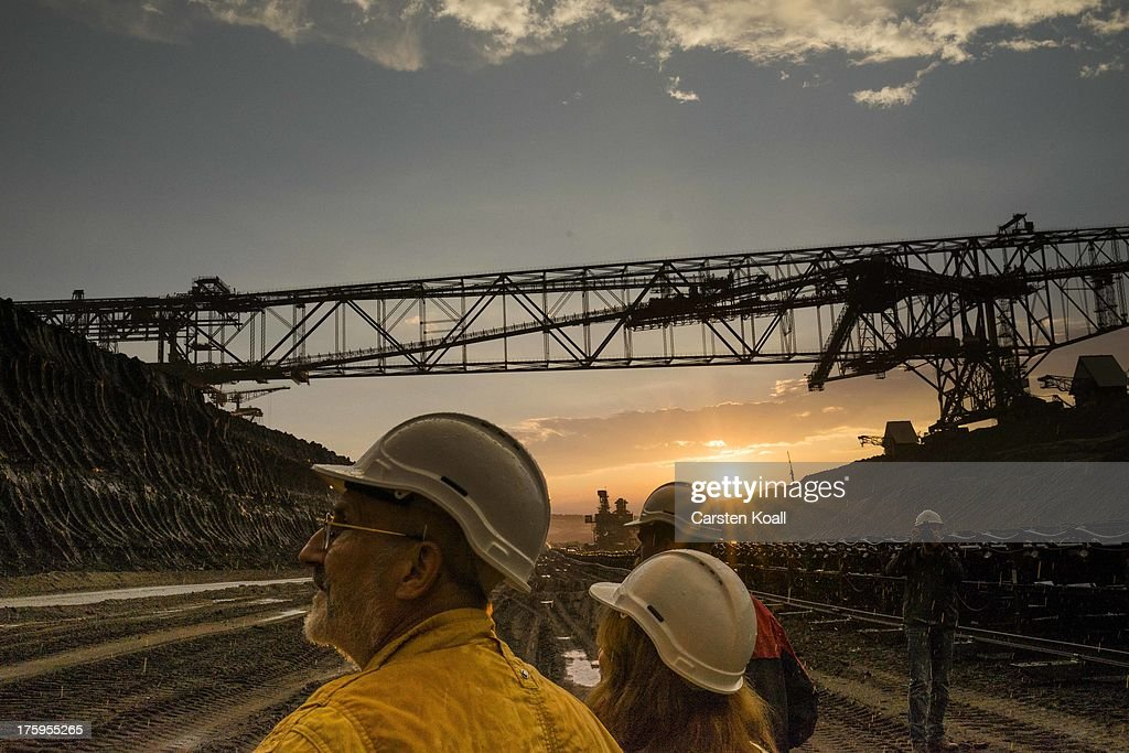 Tourists watch as a bucket wheel excavator mines lignite coal at dusk in the Welzow open-pit lignite coal mine on August 10, 2013 near Welzow, Germany. The mine, operated by Vattenfall, is one of several in the immediate area that feed a nearby power plant with coal. In a development project initiated by state government, other nearby former open-pit mines have been turned into lakes in a rejuvenation effort that is also intended to make the area a viable tourist destination.