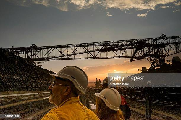 Tourists watch as a bucket wheel excavator mines lignite coal at dusk in the Welzow openpit lignite coal mine on August 10 2013 near Welzow Germany...