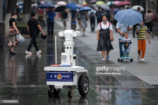 Tourists watch as a police robot patrols the Confucius Temple on July 30, 2020 in Nanjing, Jiangsu Province of China.