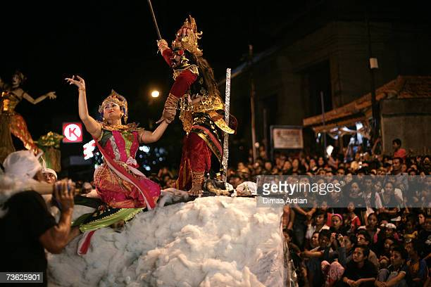 Tourists watch as Balinese men lift a giant effigy in a traditional ceremony to ward off evil spirits on the eve of Nyepi or Hindu Day of Silence on...