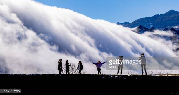 Tourists watch as clouds drift over the Jinfo Mountain after a snowfall on January 18, 2021 in Chongqing, China.