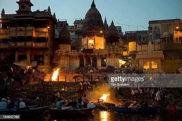 Tourists watch body bathed in River Ganges and traditional Hindu cremation on funeral pyre at Manikarnika Ghat in Holy City of Varanasi, Benares,...
