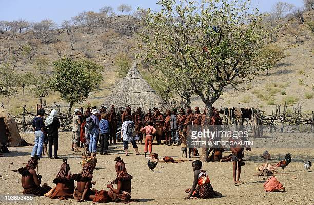 Tourists watch Himba women dance on August 19 2010 in the village of Ohungumure 15 kms west of Opuwo in northern Namibia AFP PHOTO / STEPHANE DE...