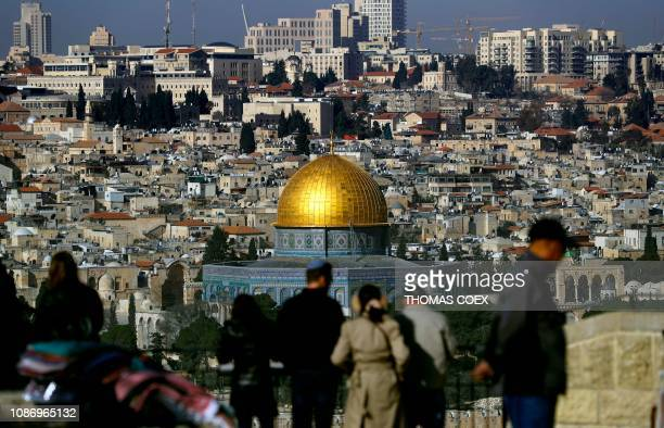 Tourists watch Jerusalem's Old City and its Dome of Rock from the panoramic view of Mount of Olives on January 23 2019