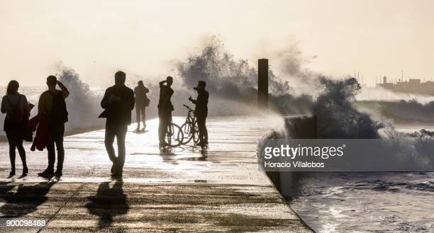 Tourists watch large waves braking into one of the wave breakers during the last day of the year in Tamariz Beach on December 31 2017 in Estoril...